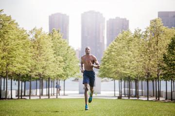 Shirtless man jogging on field