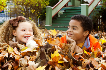 Cheerful friends looking at each other while lying on dried leaves during autumn