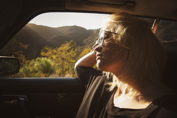 Woman leaning on window while sitting in car