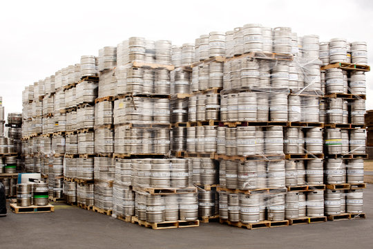 Stack of beer kegs at warehouse against clear sky
