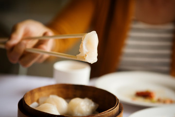 Close-up of hand holding chopsticks with Chinese dumpling