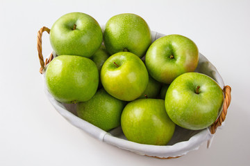 Wooden vintage basket full of green Granny Smith apples at white background