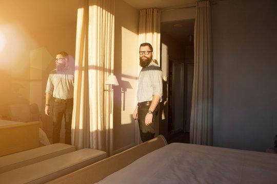 Man looking away while standing in bedroom