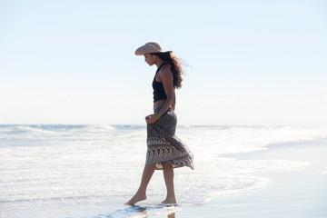 Woman in sun hat walking in sea against sky on sunny day