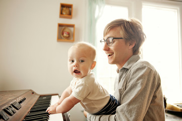Father assisting son in playing piano at home