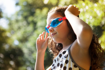 Girl with swimming goggles looking away while standing against trees