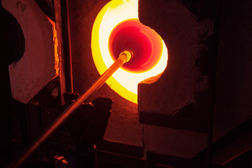 Cropped image of craftsperson heating blowpipe in furnace at glass factory