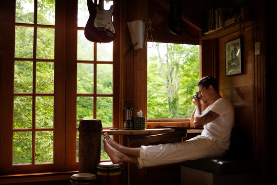 Man photographing through camera while sitting by window at home