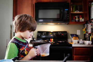 Boy looking at egg in container while standing in kitchen
