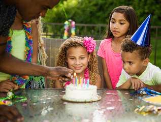 Curious children looking at birthday cake on table in backyard