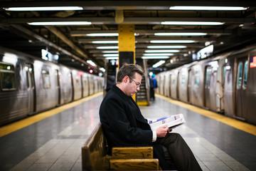 Businessman reading magazine at station