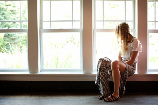 Woman looking away while sitting on window sill at home
