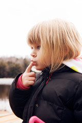 Close-up of girl touching lips with finger
