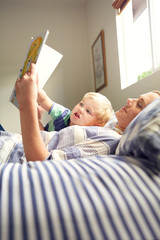 Woman with son reading book while lying on bed