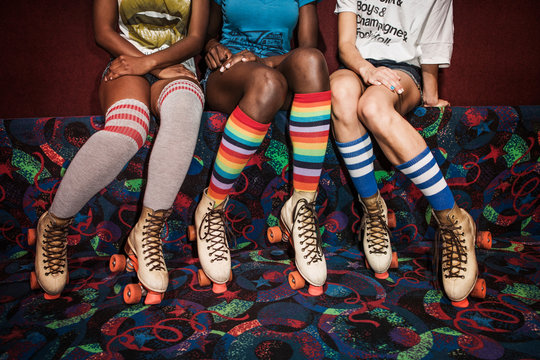 Low section of women wearing roller skates sitting on multi colored sofa