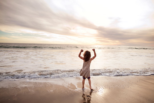 Rear view of girl with arms raised standing at shore against cloudy sky