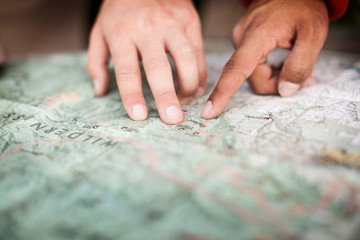 Cropped image of people pointing at map