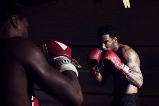 Men fighting in boxing ring