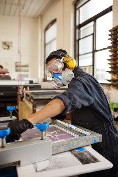 Man operating silk screen printing machinery in workshop