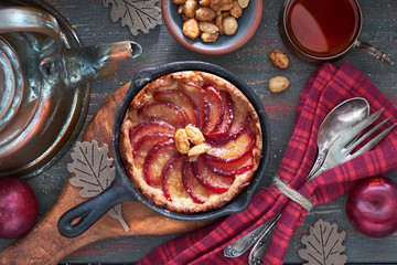 Homemade plum tart baked in iron cast skillet served with peanuts on wood