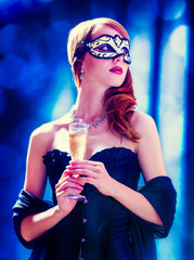 Style redhead girl in dark dress and mask with glass of drink on gray background with bokeh