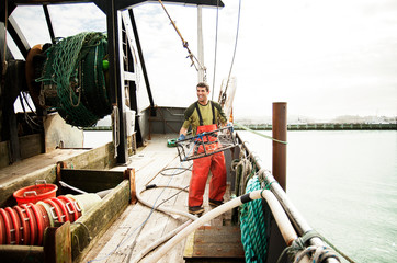 Happy man holding crab cage and standing on fishing boat