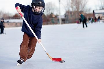 Child playing ice hockey on rink