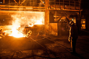 Steelworker when pouring liquid titanium slag from arc furnace