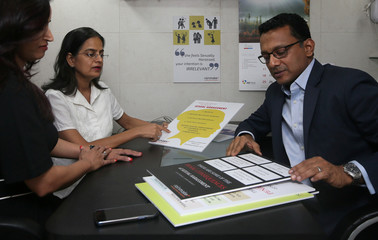 Antony Alex, CEO of consultancy firm Rainmaker, and his employees look at training material as they pose for a photograph inside his office in Mumbai