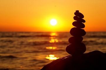 stone stacking sunset