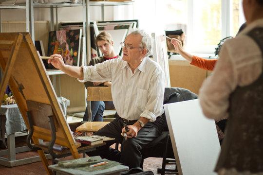 Painter teaching students at art studio