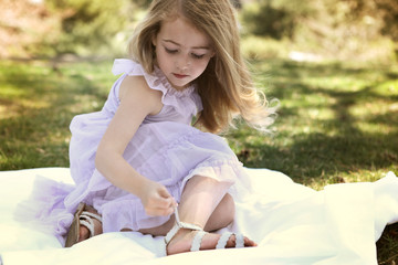 Girl adjusting sandal strap while sitting on blanket in backyard