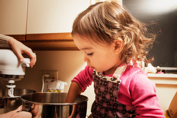 Daughter helping mother in cooking at kitchen