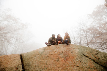 Happy friends sitting on rock in forest