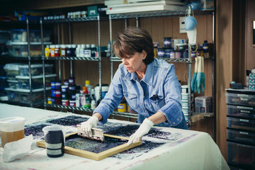 Craftswoman using silk screen to print design on fabric at workshop