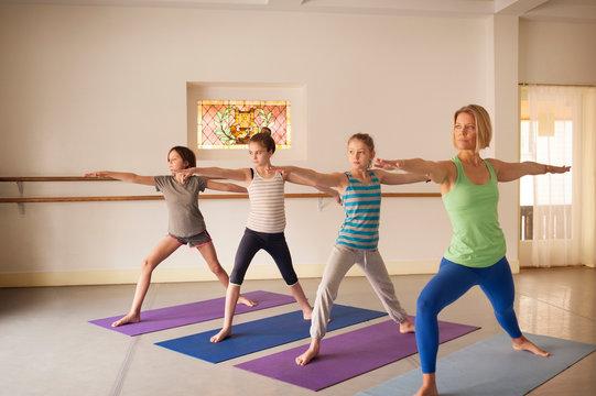 Children with trainer practicing warrior pose