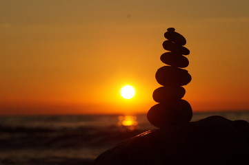 stone stacking sunset