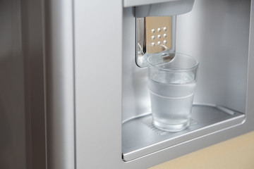 Modern cooler with glass of water, closeup