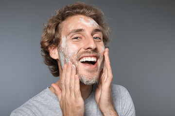 Young man washing face with soap on grey background