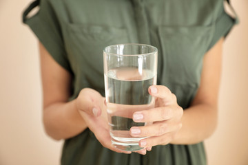 Woman holding glass with water on light background, closeup
