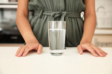 Woman with glass of water at table in kitchen, closeup