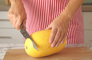 Woman cutting ripe spaghetti squash on table in kitchen, closeup