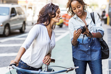 Woman showing photograph to friend while standing at city street