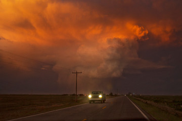 Car moving on road against cloudy sky during sunset