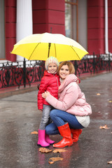 Mother and daughter with umbrella in city on autumn rainy day