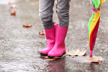 Little girl with rubber boots and umbrella after rain, focus of legs. Autumn walk