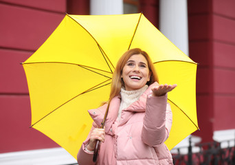 Woman with umbrella in city on autumn rainy day