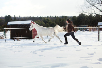 Side view of woman with horse running on snow field