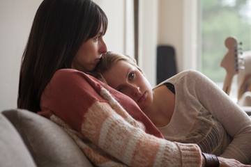 Daughter leaning mother's shoulder while sitting on sofa