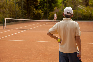 Rear view of man standing while playing tennis with woman at court